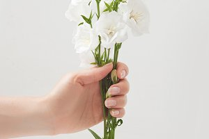 Flowers to gift. Beautiful white bells in female hands. Spring time and inspiration