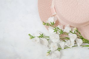 summer composition - hat, bouquet of white flowers on a white background. The concept of summer, warmth, relaxation.