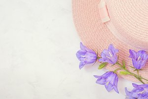 Straw hat with beautiful flowers bouquet lilac flowers . Pastel background, flatlay.