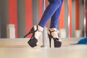 Beautiful legs of woman in black high-heeled shoes dancing on a pole in a studio