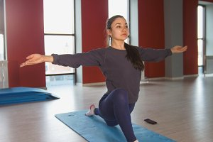 Young slender woman performs a stretching exercises on the rug in fitness room