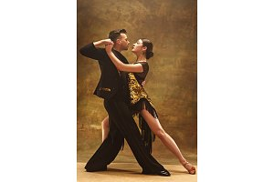 Dance ballroom couple in gold dress dancing on studio background.