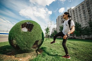 Stylish handsome man tourist is kicking the ball soccer ball of grass. Russian World cup concept