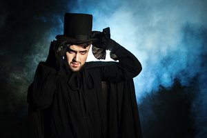 Man in a black top hat and cloak.