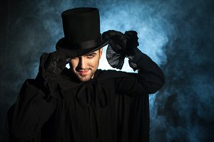 Man in a black top hat and cloak.