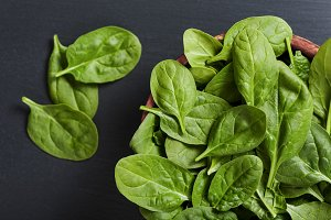 Bowl with fresh spinach leaves on natural slate background
