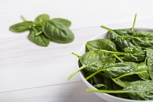 Bowl with fresh spinach leaves on white wooden table