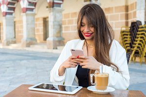 woman having a coffee with a mobile