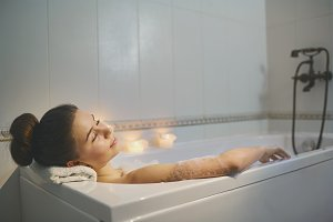 Young girl is resting in a bathtub with foam  with candles.