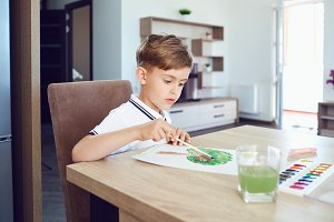 A blond boy draws on paper colored paints in the room.