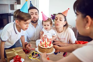 A happy family with a candle cake celebrates a birthday party