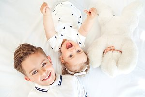 Positive children smiling lying on a white bed.