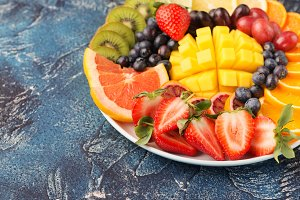 Fruits and berries platter on blue concrete table