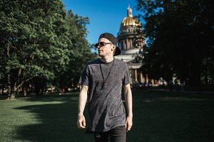 Young man tourist walking on grass near Saint Isaac's Cathedral in Saint-Petersburg in sunny summer day.
