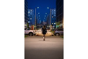 Rear view of young woman wearing black coat walking down the street, street lights towards her. A female with beautiful legs and long hair goes along the night city sidewalk