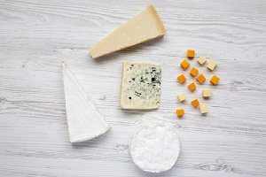 Different kinds of cheeses on white