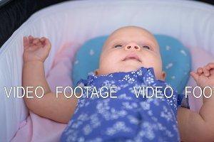 Active baby of three months in pram