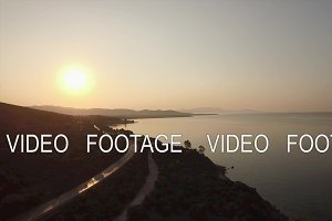 Aerial view of sea, waterfront road and upland landscape at sunset, Greece