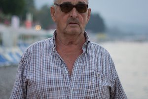 Portrait of elderly man in sunglasses by the sea on background mountains