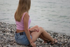 Rear view of young blonde woman sitting on the stone seashore