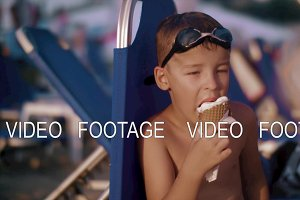 Child eating waffle cone ice cream at the beach