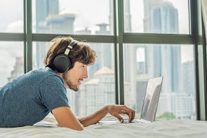 Young man is working on a laptop in his bed on a background of a panoramic window overlooking the skyscrapers. Uses wireless headphones. Freelancer, remote work, work from home