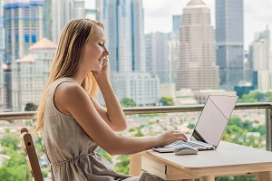 Young woman is working on a laptop on her balcony overlooking the skyscrapers. Freelancer, remote work, work from home