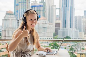 Young woman teaches a foreign language or learns a foreign language on the Internet on her balcony against the backdrop of a big city. Online language school lifestyle