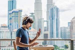 Young man teaches a foreign language or learns a foreign language on the Internet on her balcony against the backdrop of a big city. Online language school lifestyle