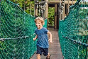 The boy is running on a suspension bridge in Kuala Lumpur, Malaysia