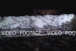 Dark foamy waves washing the seashore at night