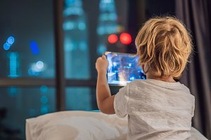 The boy uses the tablet in his bed before going to sleep on a background of a night city. Children and technology concepts