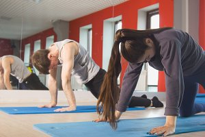 Young man and woman trains on the rug in the fitness room