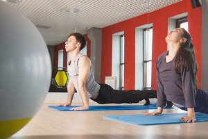 Young sportive man and young flexible woman trains on the rug in the fitness room