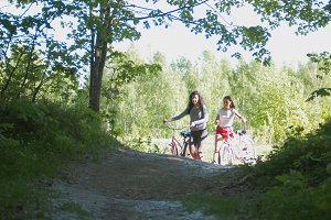 Girlfriend cyclists leave the path of the green thicket, a Sunny day
