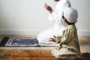 Little boy praying with his father