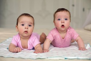 two sisters twins baby in pink clothes lying on the bed