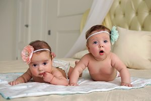 girls twins in diapers lie on the bed