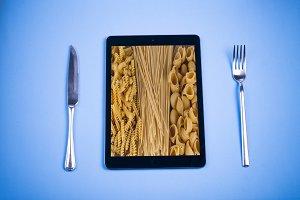Tablet, knife, fork, and food