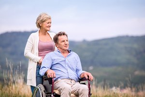 Senior woman pushing man in wheelchair, green autumn nature
