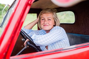 Close up of senior woman inside vintage pickup truck