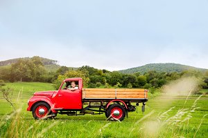 Young man inside red vintage pickup truck, green nature