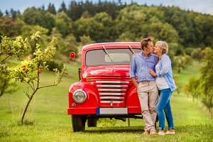 Senior couple hugging and kissing, vintage car, sunny nature