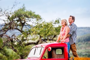 Senior couple standing in back of red pickup truck