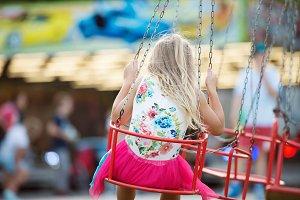 Cute little girl at fun fair, chain swing ride