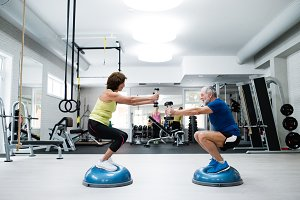 Senior couple in gym working out with weights, squatting