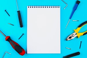 Home, House Repair, Redecorating, Renovating Concept. A set of repair tools on a blue grid: two screwdrivers and notepad, top view, flat lay.