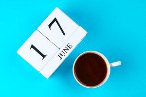 A wooden notebook with a date on June 17 and a coffee mug on a blue pastel background. Father's Day.