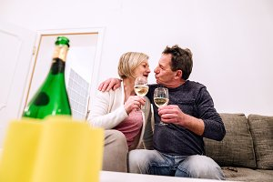 Senior couple sitting in living room , drinking champagne, kissi