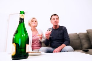 Senior couple sitting in living room , drinking champagne